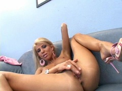 Busty babe Clara G rubs her twat with her fingers in the couch