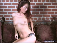 Brunette babe Nakita Kash plays with her tiny tits on the couch