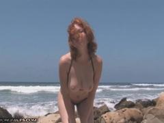 Beach babe in a brief bikini struts her stuff