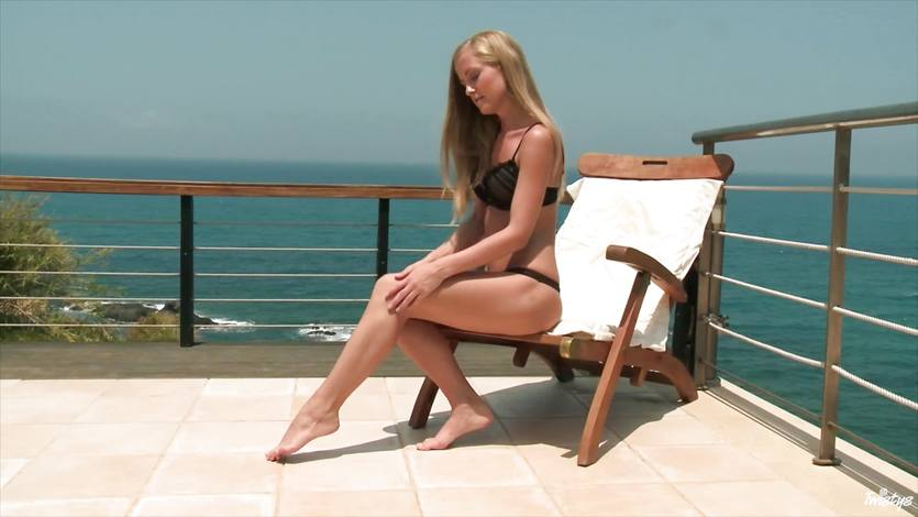 Blonde hottie fiddles with her pussy in the sun