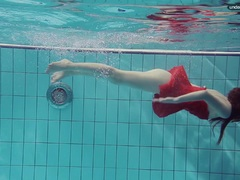 Cute Red Dressed teen swimming with her eyes opened